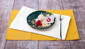 Sweet cold dessert and a white flower on a colorful table background. Vanilla ice cream with raspberries, mint and nuts. Stock Image