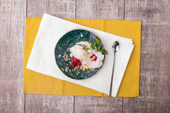 Sweet cold dessert and a white flower on a colorful table background. Vanilla ice cream with raspberries, mint and nuts. Stock Photos