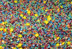 Sweet colorful confectionery sprinkling texture with yellow stars. Sugar sprinkle dots, decoration for cake and bakery royalty free stock images