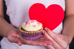 Sweet colorful cupcake and red heart in female hands Royalty Free Stock Images