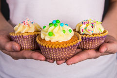 Sweet colorful cupcakes with butter cream in female hands Royalty Free Stock Photography