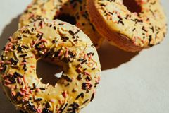 Sweets food - yellow donuts biscuits on gray background stock images