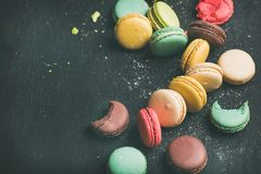 Sweet colorful French macaroon cookies variety with sugar powder. Over black background, top view, selective focus, copy space royalty free stock photo