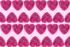 Sweet colorful lollipops. Sweet red heart Spiral Lollipop On pink Background Royalty Free Stock Photo