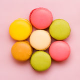 Sweet colorful macaroons against pink background. Stock Photos