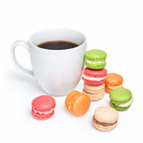 Sweet and colorful macaroons with cup of coffee on white background. Traditional french dessert macarons.  Royalty Free Stock Photography