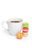 Sweet and colorful macaroons with cup of coffee on white background. Traditional french dessert macarons, space for text.  Royalty Free Stock Images