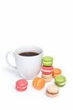 Sweet and colorful macaroons with cup of coffee on white background. Traditional french dessert macarons, space for text.  Royalty Free Stock Image