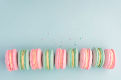 Sweet colorful macaroons in row on blue background. With copy space. Flat lay Stock Photography
