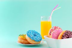 Sweet and colorfully decorated donuts and a glass of orange juice for kids royalty free stock images