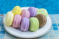 Sweet and colourful french macaroons on dish with blue sky swimm Stock Photo