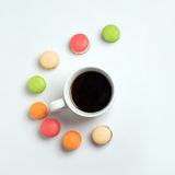 Sweet and colourful macaroons with cup of coffee on white background. Traditional french dessert. Top view, flat lay Stock Image