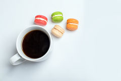 Sweet and colourful macaroons with cup of coffee on white background. Traditional french dessert. Top view, flat lay Stock Images