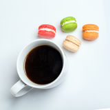 Sweet and colourful macaroons with cup of coffee on white background. Traditional french dessert. Top view, flat lay. Space for text Royalty Free Stock Photo
