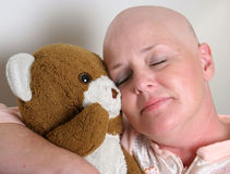 Sweet Comfort. A medical patient cuddling with a teddy bear for comfort royalty free stock photography