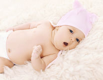 Sweet comfortable baby in hat yawns lying on the bed Royalty Free Stock Images