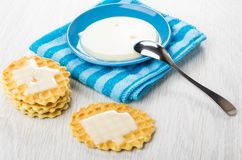 Sweet condensed milk in saucer, milk on wafer cookies, teaspoon. Sweet condensed milk in blue saucer on napkin, milk on wafer cookies, teaspoon on wooden table Stock Photography