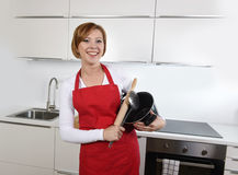 Sweet cook woman wearing red apron holding cooking pot and rolling pin at home kitchen smiling happy Stock Image
