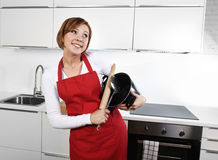 Sweet cook woman wearing red apron holding cooking pot and rolling pin at home kitchen smiling happy Stock Photos