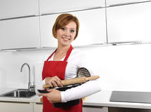 Sweet cook woman wearing red apron holding cooking pot and rolling pin at home kitchen smiling happy Stock Photo