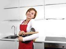 Sweet cook woman wearing red apron holding cooking pot and rolling pin at home kitchen smiling happy Royalty Free Stock Photo