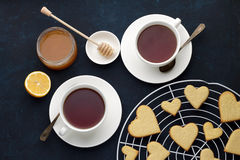 Sweet cookies in heart shape with two cups of tea, honey and lemon on dark blue background Valentines day. Stock Photos