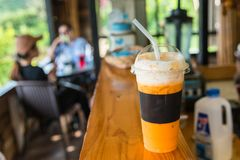 The sweet cooled thai tea drink with ice on shop counter background. royalty free stock photo