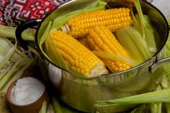 Sweet corn boil with salt. cooked sweet corn in pot on wooden table. Sweet corn boil with salt. cooked sweet corn in pot on wooden table royalty free stock photography