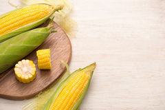 Sweet corn on cobs on cutting board on wooden table. Sweet corn on cobs on cutting board on wooden table Royalty Free Stock Image