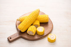 Sweet corn on cobs on cutting board on wooden table. Sweet corn on cobs on cutting board on wooden table royalty free stock photo