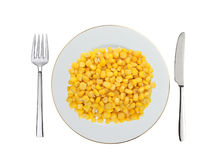 Sweet corn grain on white plate with knife and fork isolated on Stock Photography