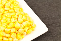 Sweet Corn. Kernels in a white plate. On black surface Royalty Free Stock Images
