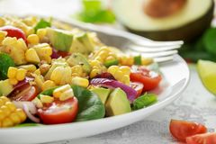 Sweet Corn salad with tomatoes, avocado, red onion, herbs and lime stock image