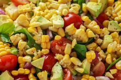 Sweet Corn salad with tomatoes, avocado, red onion, herbs and lime stock photography