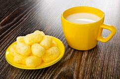 Sweet corn sticks in yellow glass saucer, cup with milk on wooden table