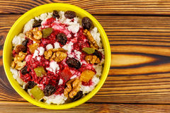 Sweet cottage cheese dessert with raspberry jam, nuts, raisins, candied in bowl on wooden table, top view Stock Images