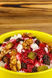 Sweet cottage cheese dessert with raspberry jam, nuts, raisins, candied in ceramic bowl on wooden table, selective focus Stock Photo