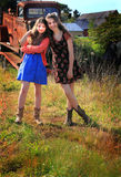 Sweet Country Girls. Two happy teenage country girls wearing dresses, hanging out in front of a rusty old truck. Shallow depth of field Royalty Free Stock Photography
