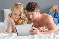 Sweet Couple on Bed Watching Something in Tablet Royalty Free Stock Image