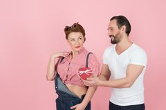 Sweet couple choosing the heart. Man in white t-shirt presenting his heart to brunette woman in denim. Guy gives heart-box to girl. Sweet couple choosing the Stock Photo