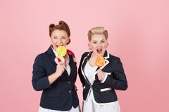 Sweet Couple of girls with lollipops. Pin-up styled women with candies in hand. Two sweet ladies with two sweets. Royalty Free Stock Photo