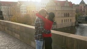 Sweet couple have romantic date in old european town on the sunset bridge. Young lovers kissing and enjoying time