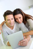 Sweet couple at home using a tablet Royalty Free Stock Photos