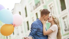 Sweet couple kissing in street, romantic date with colorful balloons, happiness. Stock video Stock Images