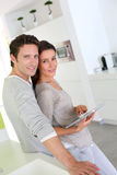 Sweet couple in kitchen using tablet Stock Image