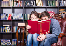Sweet Couple at the Library Hiding Behind a Book Stock Image