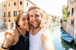 Sweet couple in love taking a selfie in Venice Italy while traveling around europe. Happy couple taking a selfie with smart mobile phone in the canals of Venice royalty free stock photography