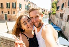 Sweet couple in love taking a selfie in Venice Italy while traveling around europe. Happy couple taking a selfie with smart mobile phone in the canals of Venice stock photo