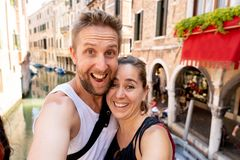 Sweet couple in love taking a selfie in Venice Italy while traveling around europe. Happy couple taking a selfie with smart mobile phone in the canals of Venice stock photography