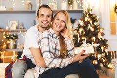 Sweet couple opening Christmas gifts stock image